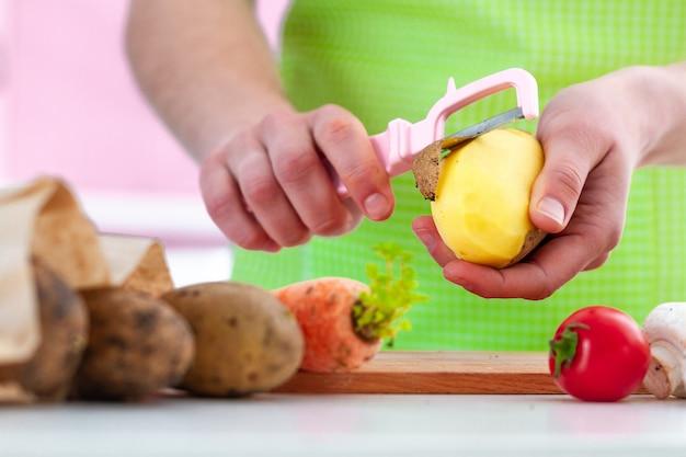 Dona de casa no avental que descasca batata madura com um descascador para cozinhar pratos de legumes frescos em casa.