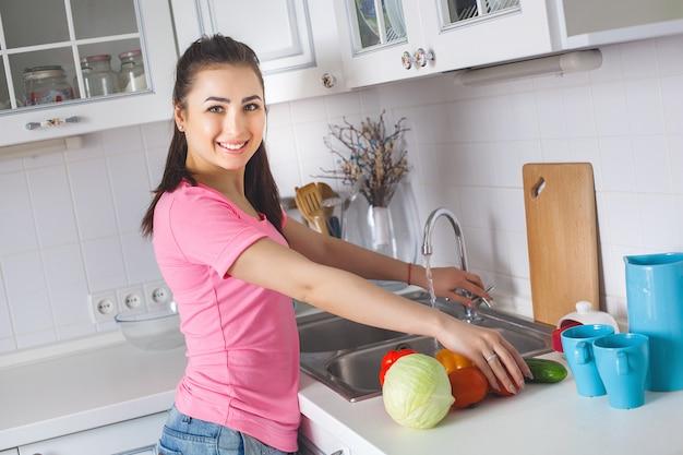 Dona de casa nova que lava legumes frescos