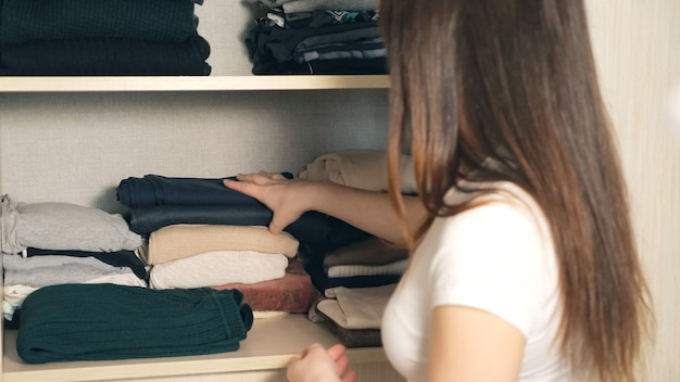 Dona de casa organizando roupas no guarda-roupa, close-up