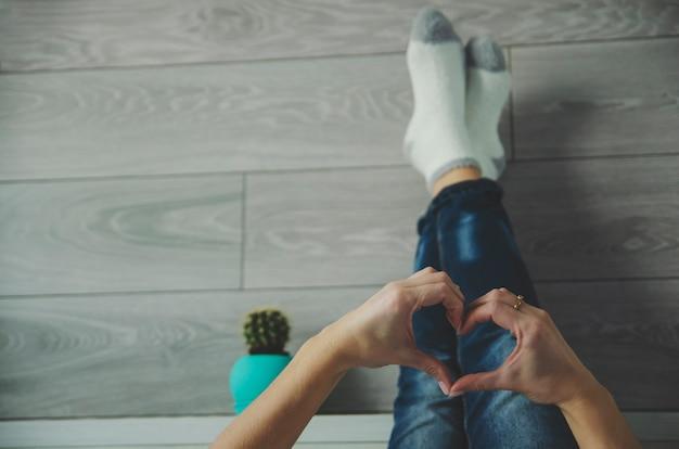 Dona de casa ou jovem mulher deitada com as pernas na cama no quarto e formando um coração