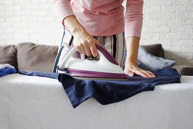 Dona de casa passando roupa com ferro e tábua de passar em casa