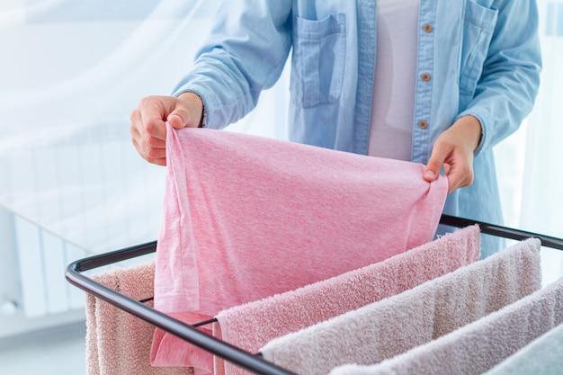 Dona de casa pendura roupa molhada na secadora de roupas