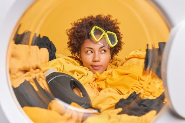 Dona de casa pensativa, de cabelos cacheados, focada e com expressão pensativa, usa máscara de mergulho na testa carrega máquina de lavar com roupa suja faz as tarefas domésticas diárias