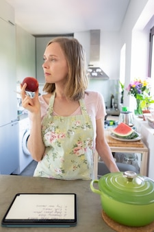 Dona de casa pensativa segurando frutas e desviando o olhar enquanto cozinha na cozinha, usando o tablet perto da panela no balcão. vista frontal, foto vertical. cozinhando em casa e conceito de alimentação saudável