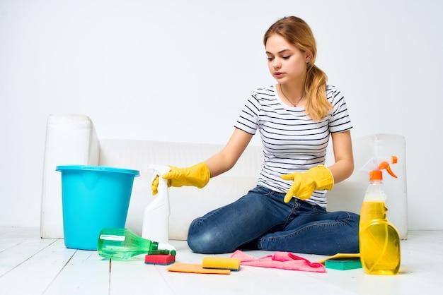 Dona de casa perto da sala do sofá limpando fundo claro