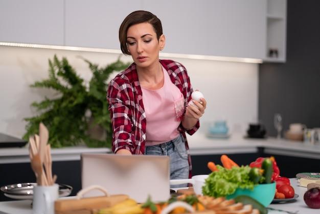 Dona de casa pesquisando receitas on-line usando um laptop enquanto cozinha ou assa segurando ovos