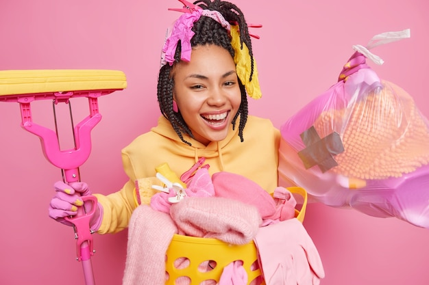 Dona de casa positiva com sorrisos de dreadlocks coleta amplamente lixo