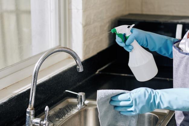 Dona de casa pulverizando torneira de cozinha