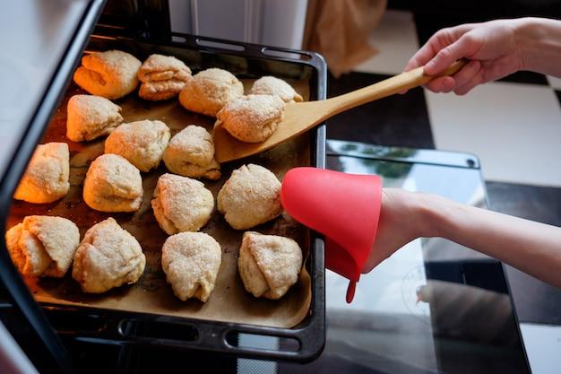 Dona de casa saindo do forno prepeared biscoitos assados