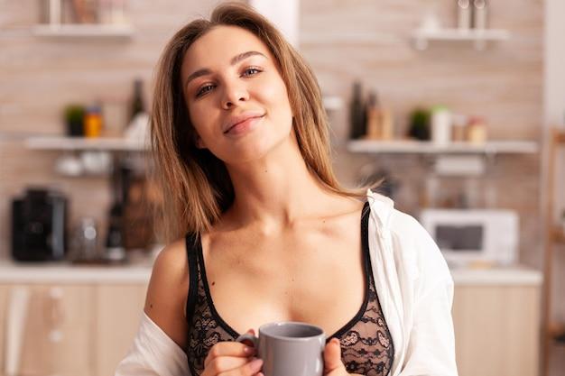 Dona de casa sedutora relaxando durante o café da manhã sentado na cozinha moderna e aconchegante. jovem mulher atraente com tatuagens em lingerie sedutora, segurando uma xícara de chá relaxante na cozinha sorrindo.