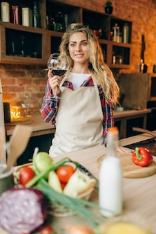 Dona de casa segurando uma taça de vinho tinto nas mãos