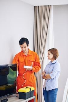 Dona de casa séria, técnica de controle instalando roteador wi-fi no quarto