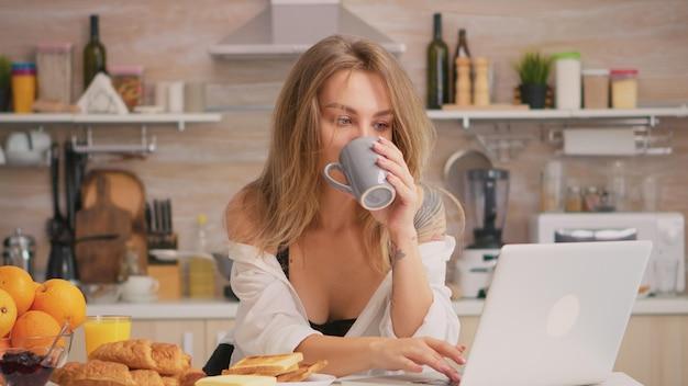 Dona de casa sexy com tatuagens usando laptop vestindo cueca sedutora, bebendo café pela manhã. mulher loira atraente em lingerie preta segurando uma xícara de chá durante o café da manhã, aproveitando o tempo.