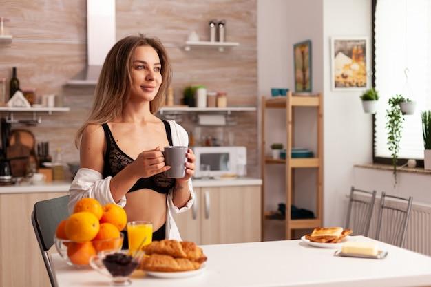 Dona de casa sexy em lingerie relaxante após preparar o saboroso café da manhã.