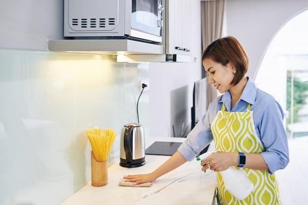 Dona de casa sorridente espalhando detergente de limpeza na superfície do balcão da cozinha e limpando-o com um pano macio