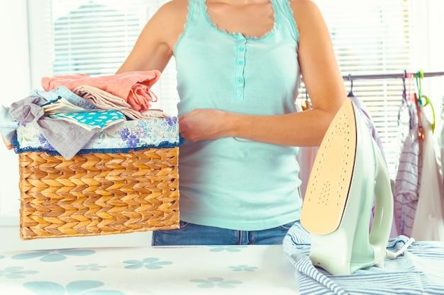 Dona de casa, trazendo uma enorme pilha de roupa na tábua de passar