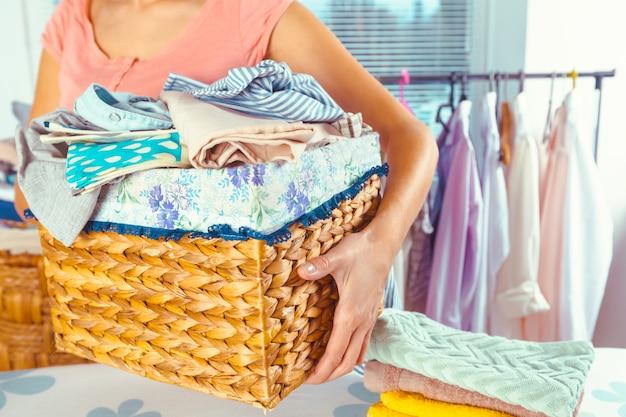 Dona de casa, trazendo uma pilha enorme de roupa na tábua de passar
