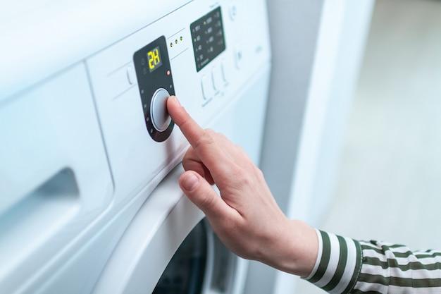 Dona de casa usando a tela e o botão para ligar e escolher o programa de ciclo na máquina de lavar para lavar roupa em casa.