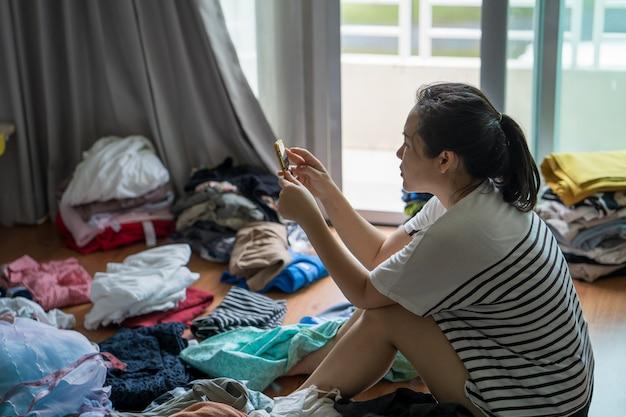 Dona de casa usando celular enquanto dobra roupas