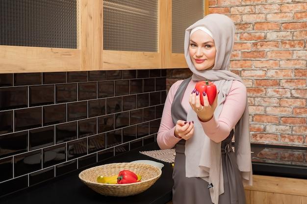 Dona de casa usando hijab segurando e mostrando pimenta na mão na cozinha
