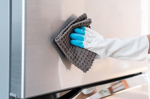 Dona de casa usando luva protetora de borracha com pano para limpar a superfície da geladeira em casa