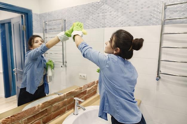 Dona de casa woking em casa. senhora com uma camisa azul. mulher em um banheiro.