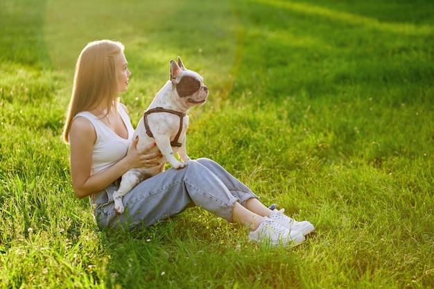 Dona de uma cadela segurando um buldogue francês de joelhos ao ar livre