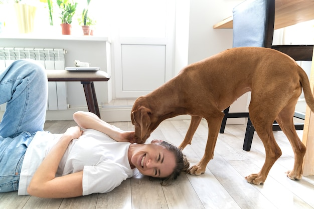 Dona de uma mulher feliz brincando com seu adorável cachorro vizsla, se abraçando, beijando, deitada no chão em casa