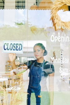 Dona triste fechando sua loja