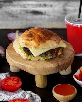 Doner de carne com pão servido com ketchup e coque