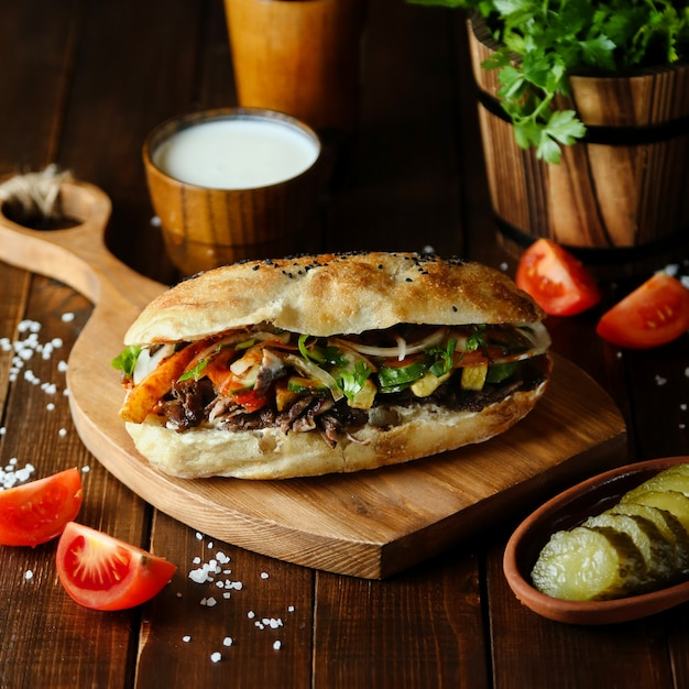 Doner de carne no pão na placa de madeira