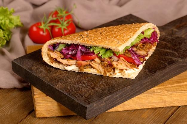 Doner de frango no pão em uma placa de madeira