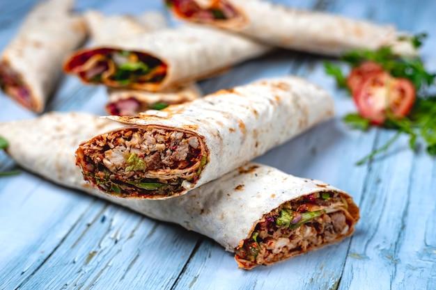 Doner de frango vista lateral com cebola pepino alface e molho em pão árabe em cima da mesa