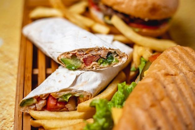 Doner de frango vista lateral com pepino molho de tomate em pita e batata frita em cima da mesa