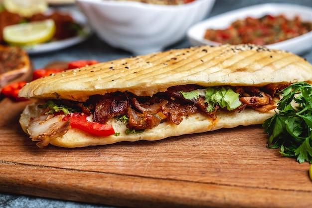 Doner de frango vista lateral com tomate verdes e alface no pão