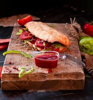 Doner de pão tandir, sucuk ekmek com salsicha em uma placa de madeira