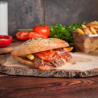 Doner de vista lateral com tomate e batatas fritas e verduras em panelas