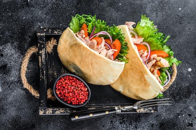 Doner kebab com carne de frango grelhado e vegetais no pão pita em uma bandeja de madeira.