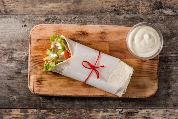 Doner kebab ou sanduíche shawarma na vista superior de mesa de madeira