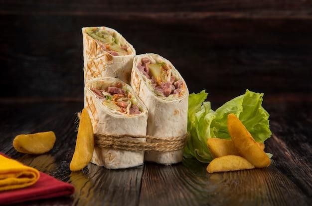 Doner kebab, shawarma com batatas rústicas e repolho em um fundo de textura de madeira