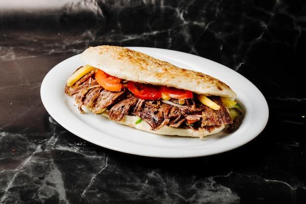 Doner turco no pão tandir dentro da placa branca.