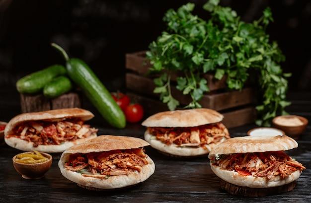 Doner turco servido dentro de pães sobre uma mesa de madeira rústica