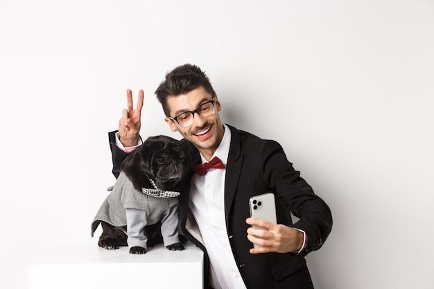 Dono de cachorro alegre em terno comemorando ano novo com cachorro, tirando selfie em smartphone perto de um pug preto fofo fantasiado de fundo branco