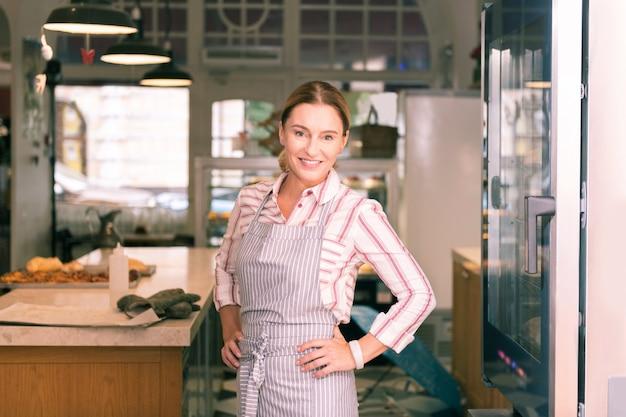Dono de padaria. dono de uma padaria bem-sucedido, usando avental listrado, trabalhando duro pela manhã