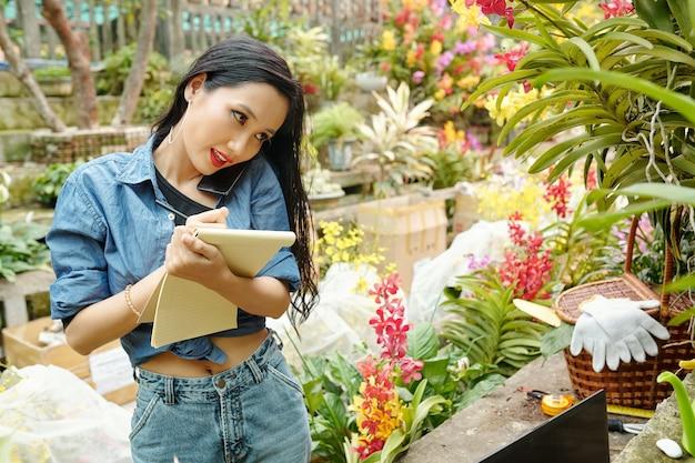Dono de um viveiro de flores vietnamita muito positivo falando ao telefone com o cliente e anotando os detalhes do pedido