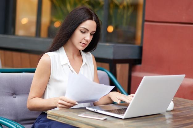 Dono de uma empresa séria, concentrada em documentos, lê atentamente os termos do contrato, usa o laptop, passa o jantar no café ao ar livre.