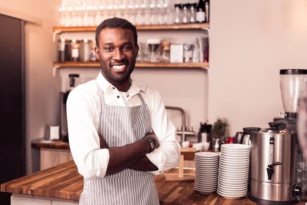 Dono do negócio. homem alegre e simpático usando um avental enquanto trabalha em seu próprio café