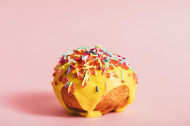 Donut amarelo redondo pequeno com granulado colorido