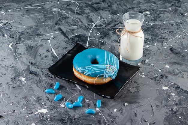 Donut azul com cobertura de creme e copo de leite na mesa de mármore.