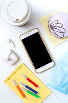 Donut, café, fones de ouvido, máscara médica e materiais em uma mesa de escritório branca